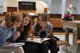 Charlotte (v.l.), Janna und Paulina studieren ihre Konfirmandenmappe in der Lutherkirche (Foto: J. Gerhardt)