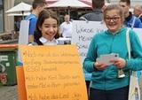 Eine zukünftige Konfirmandin aus der Lutherkirche lässt sich als Dietrich Bonhoeffer von den Gottesdienstbesuchern erraten. Als Belohnung verteilt ihre Freundin Postkarten. (Foto: M. Böschemeyer)